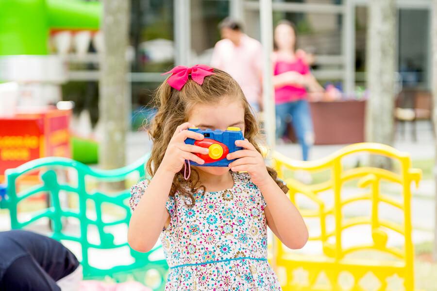 menina brincando com uma maquina de brinquedo