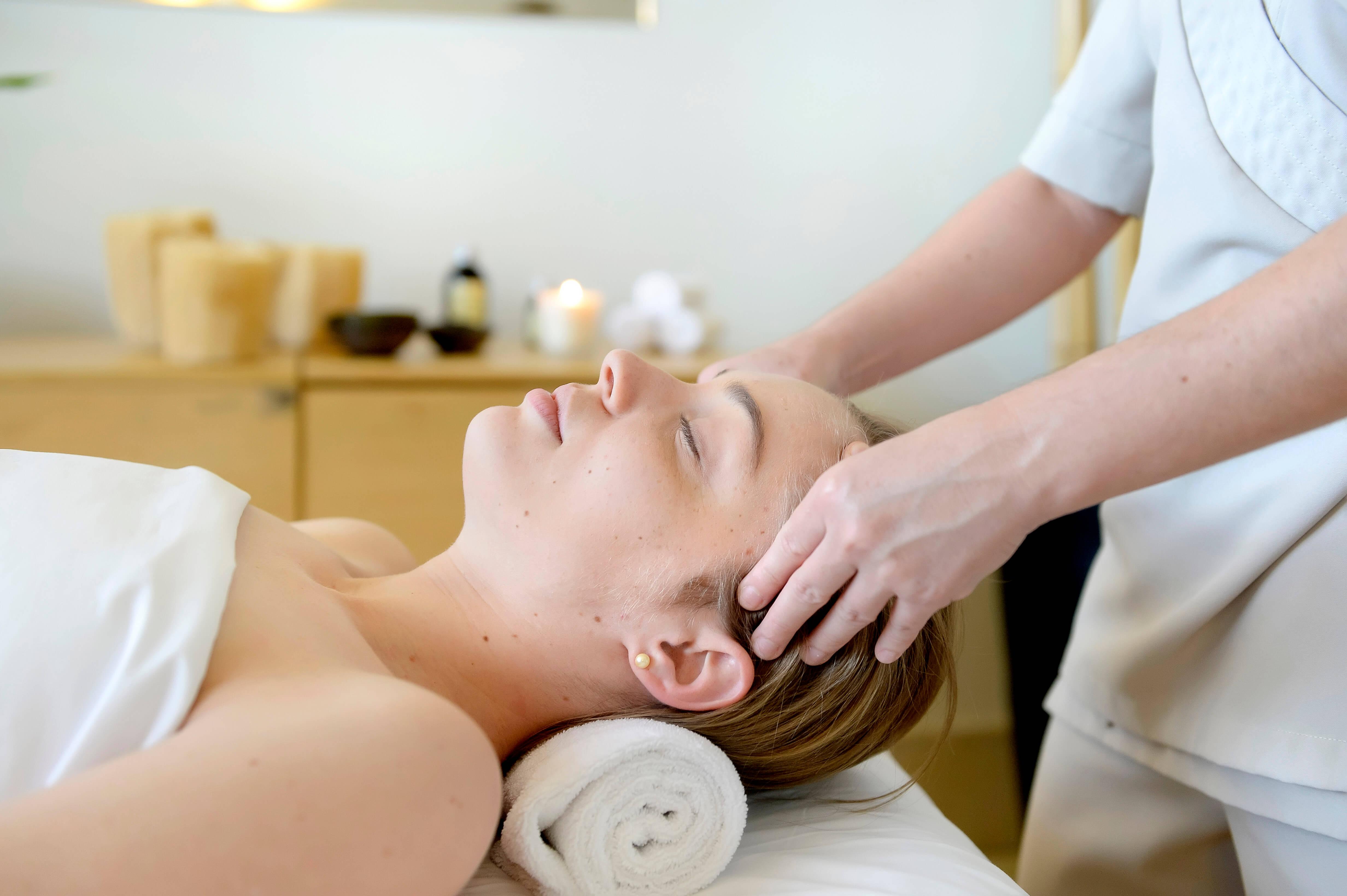 cliente sendo massageada na cabeça por uma profissional