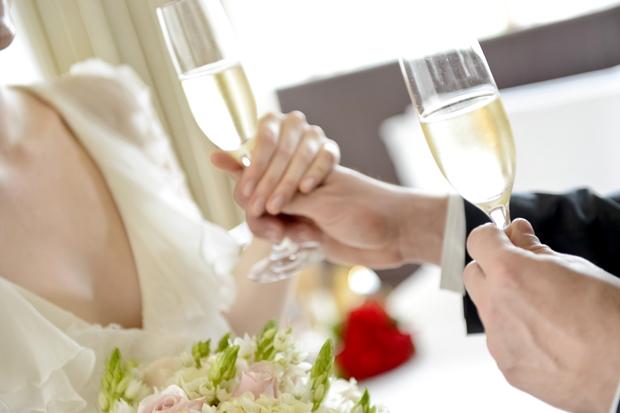 mãos de noivos com taças de champagne