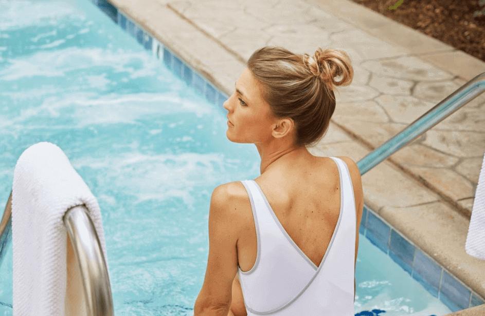 mulher de maiô branco sentada na escada da piscina