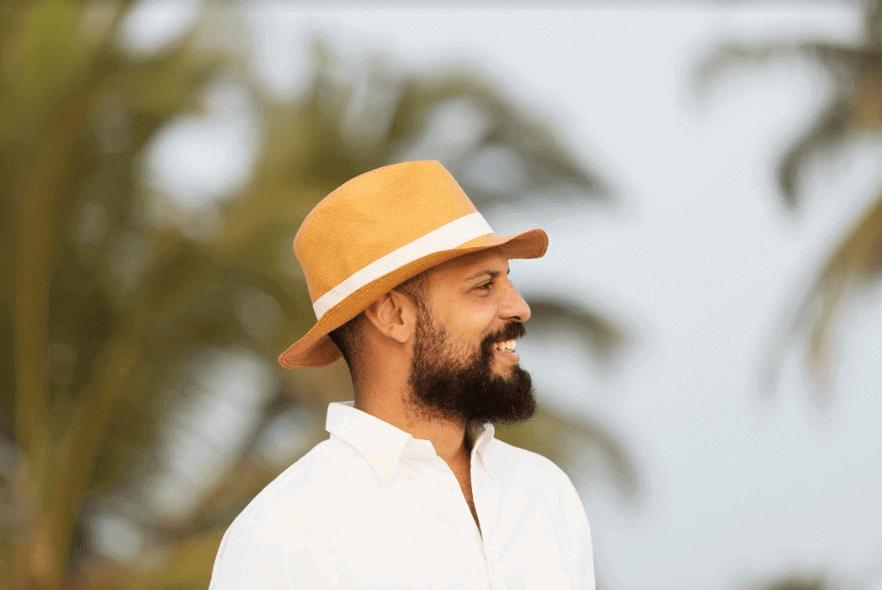 homem de chapéu sorrindo de perfil