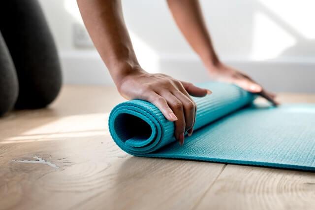 A imagem mostra uma pessoa enrolando um tapete de yoga