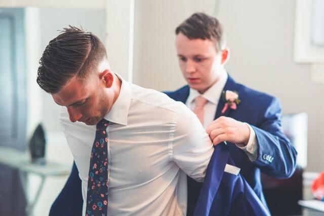 Noivo recebendo ajuda para colocar o terno