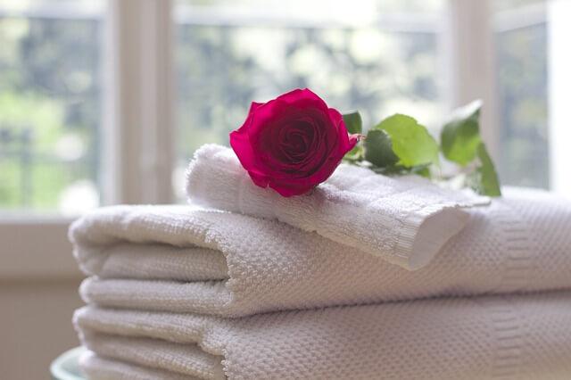 Toalhas dobradas com uma rosa em cima