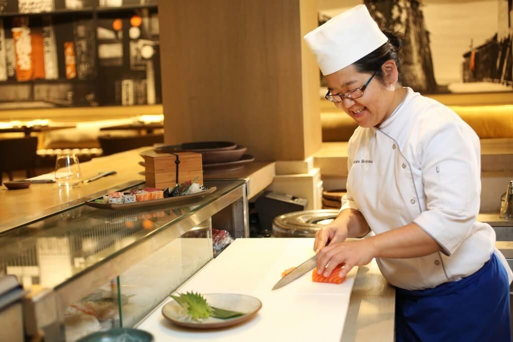 Mulher sushiwoman preparando prato de comida japonesa