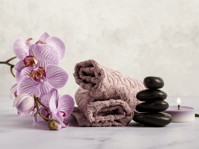 Flores, pedras quentes e toalha no spa para relaxar,