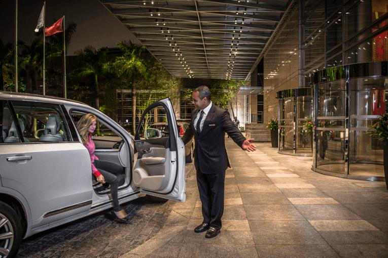 funcionário do hotel recebendo o hospede segurando a porta do carro