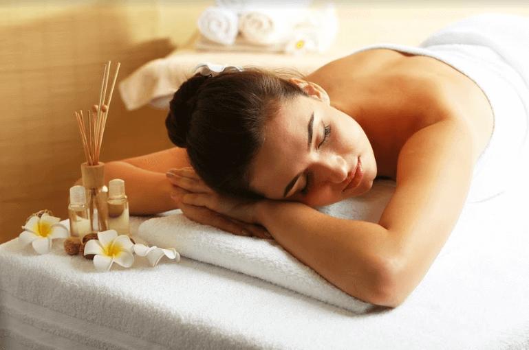 mulher deitada em uma maca de massagem com toalha nas costas