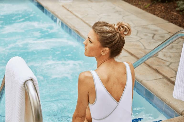 mulher de maiô branco sentada na beira da piscina de perfil