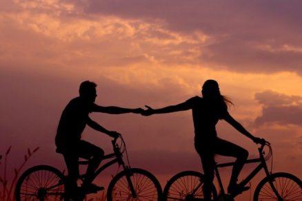 casal andando de bicicleta e dando as mãos