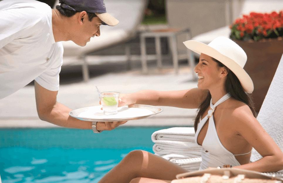profissional servindo uma cliente relaxando na cadeira da piscina