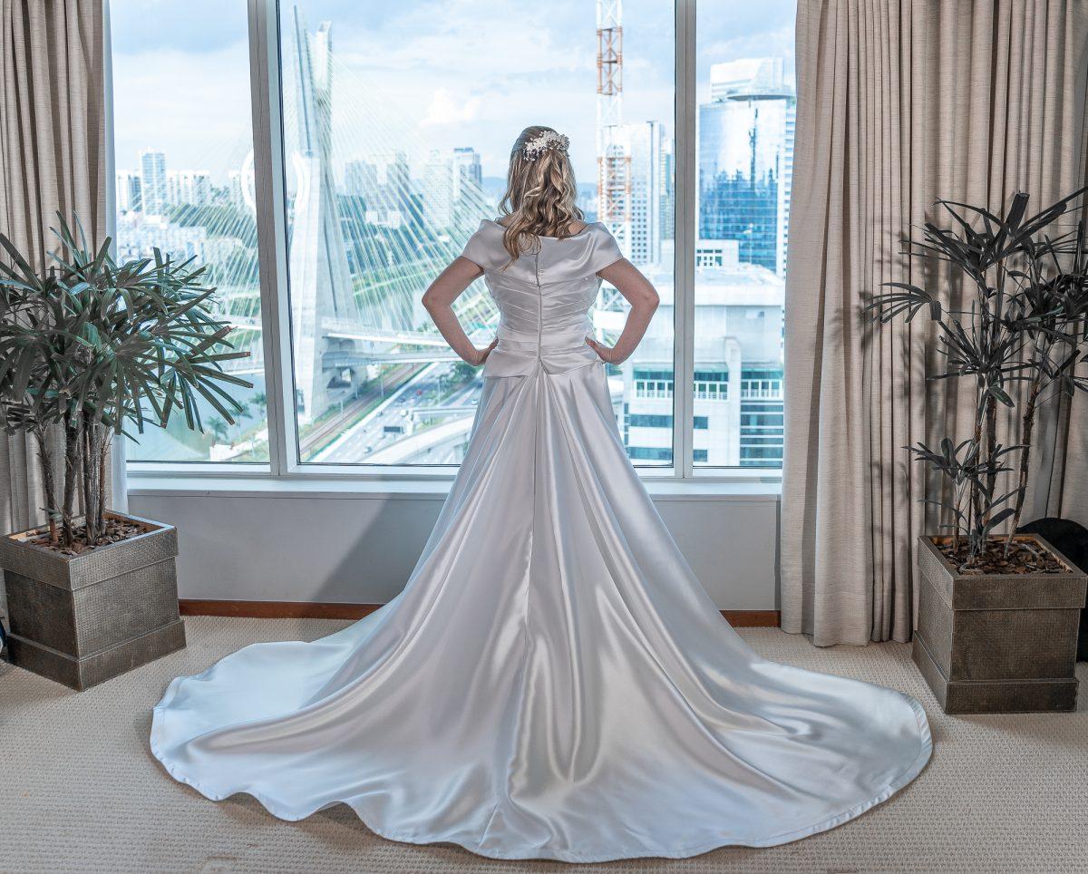 Na imagem, há uma mulher, vestida de noiva, de costas, em um quarto de hotel. Ao fundo, a ponte estaiada em São Paulo