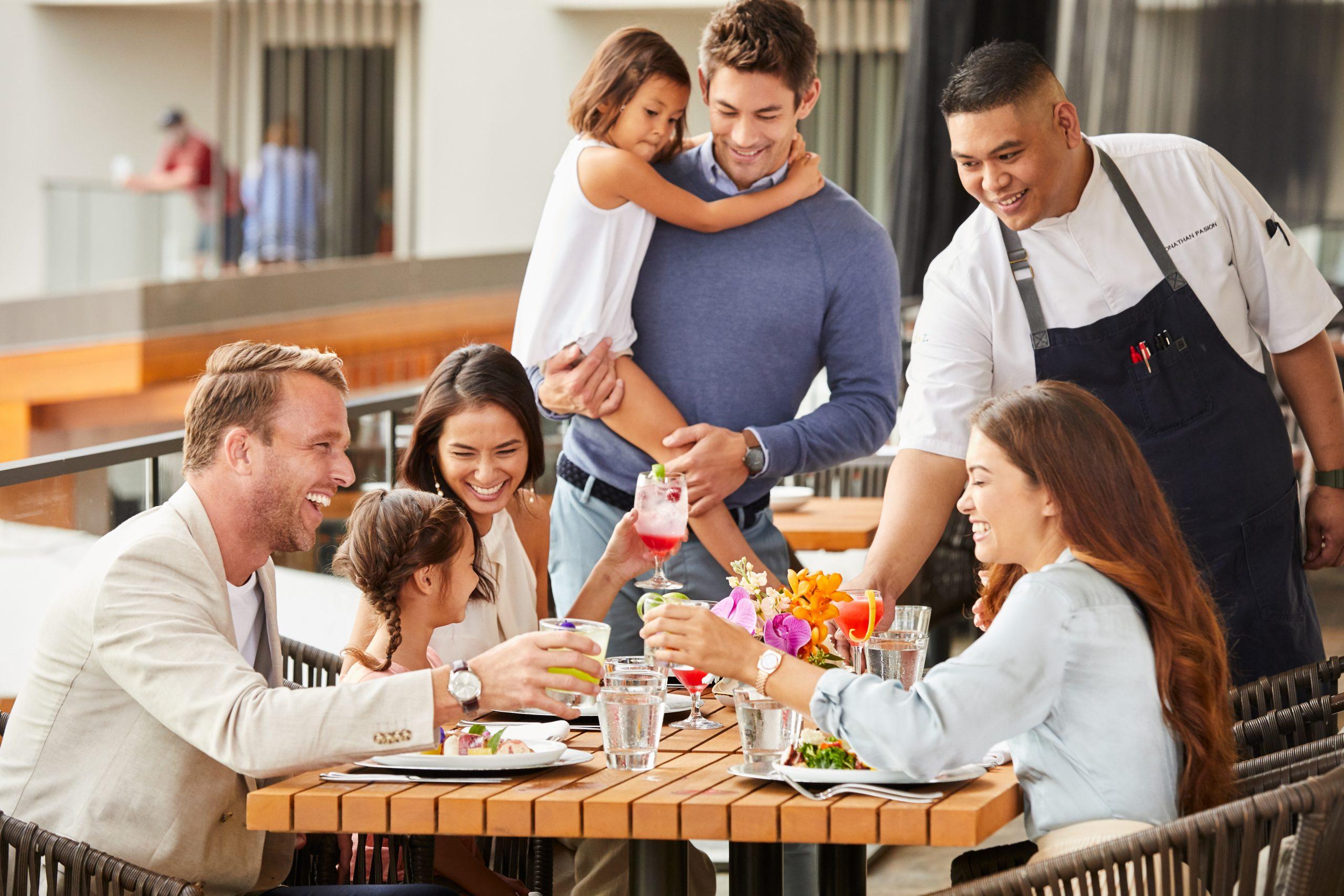 A imagem mostra uma família sentada à mesa, fazendo uma refeição no restaurante, enquanto o garçom está servindo os alimentos