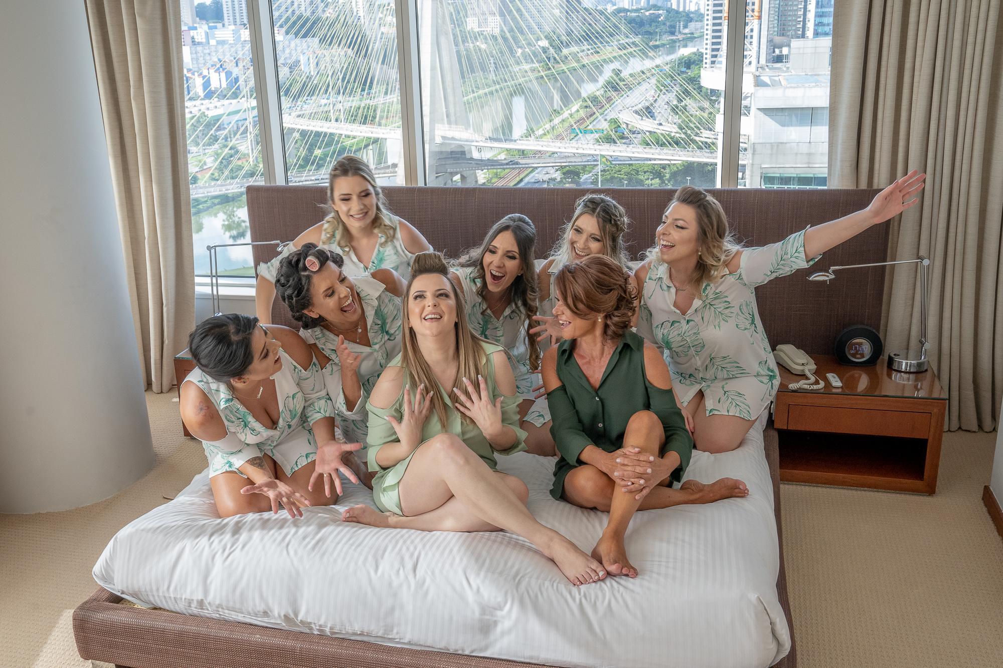 Na imagem, é possível ver oito mulheres sentadas em uma cama, do hotel, todas em volta da noiva, que está ao centro sorrindo