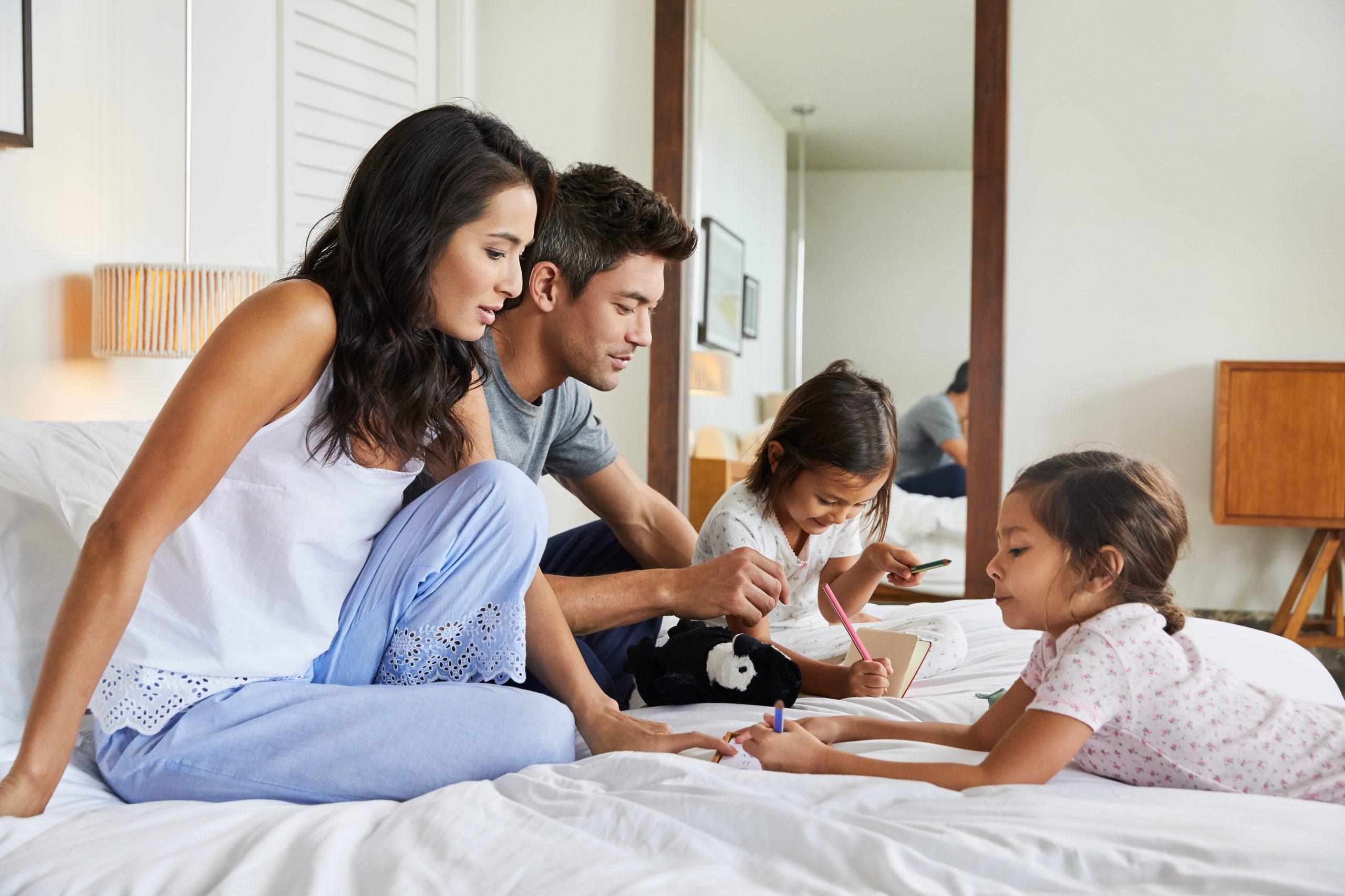 Na imagem, há uma família sentada na cama do hotel, com um homem, uma mulher e duas crianças, que estão pintando desenhos
