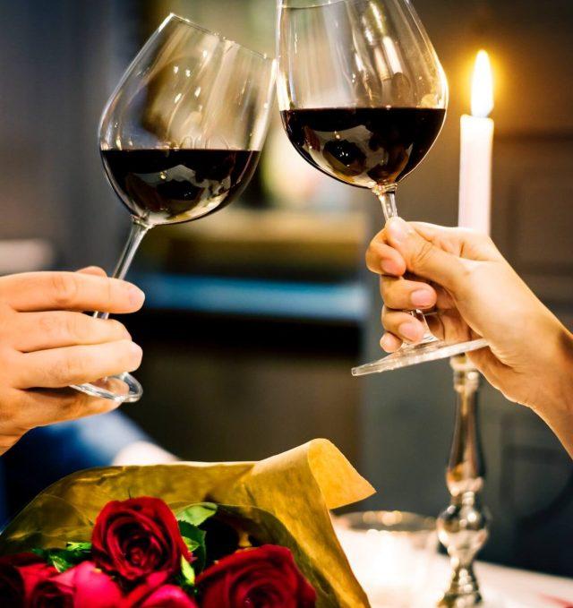 Casal brindando com taça de vinho com rosas sobre a mesa