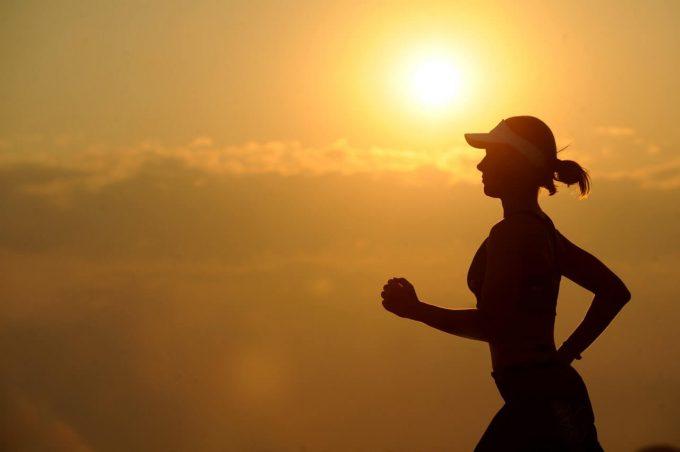 Mulher correndo no pôr do sol