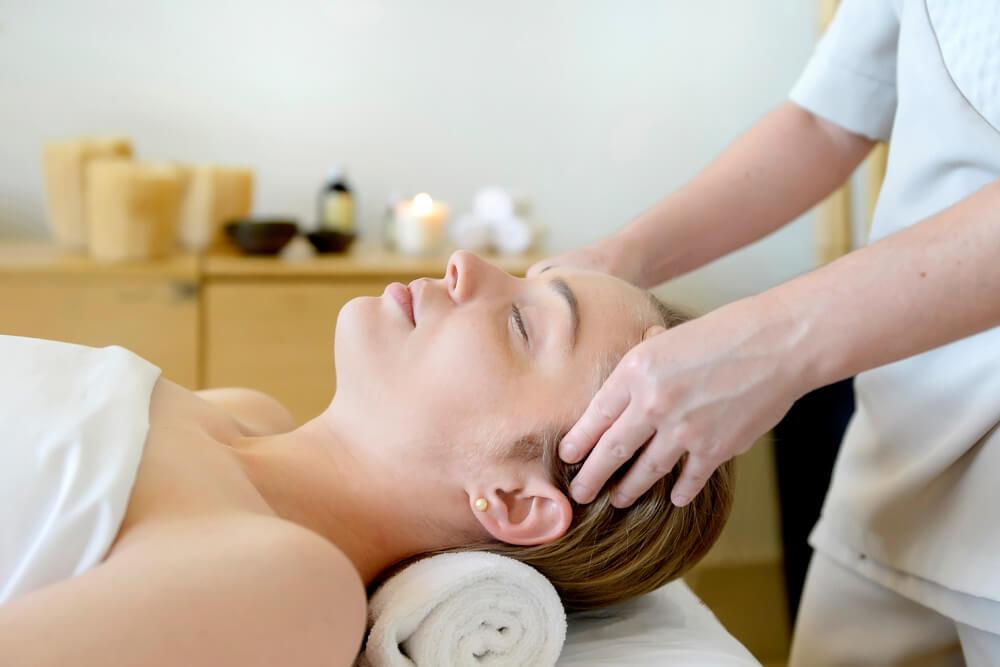 Mulher deitada recebendo massagem no rosto