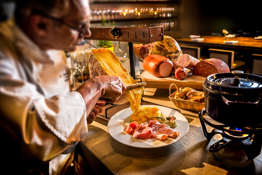 Cozinheiro servindo queijo raclette