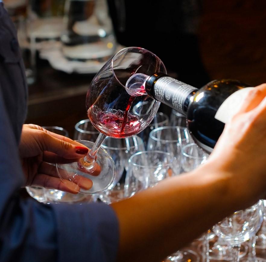 Mulher servindo vinho na taça