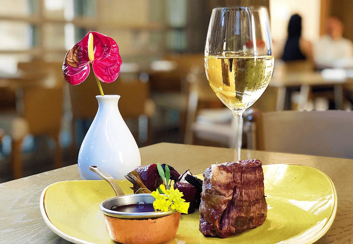 Peça de carne com beterrabas e recipiente de molho sobre prato amarelo. Ao lado, uma taça de vinho branco e decoração de flor vermelha em vaso branco.