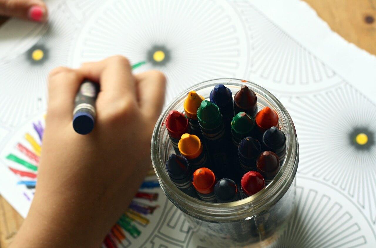 Criança pintando desenho de recreação com giz de cera