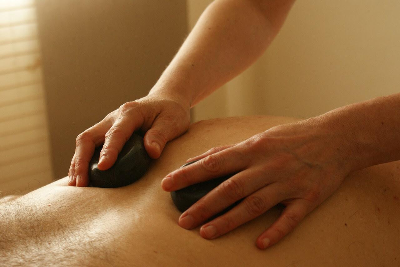 Pessoa recebendo massagem com pedras quentes
