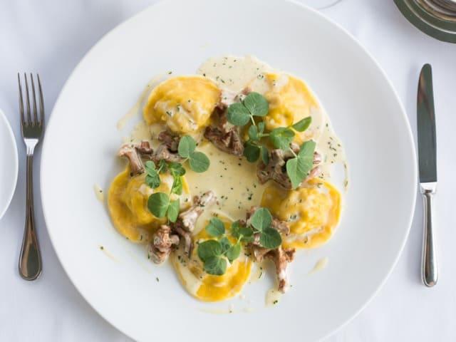 Prato de ravioli de carne com molho de cogumelos.
