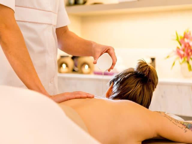 Mulher recebendo massagem de profissional do Grand Hyatt Rio de Janeiro